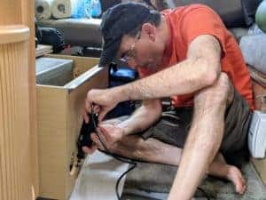 man cutting wooden box to install RV safety detector