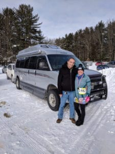 Couple with van in snowy parking lot