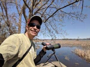 man with spotting scope in marsh