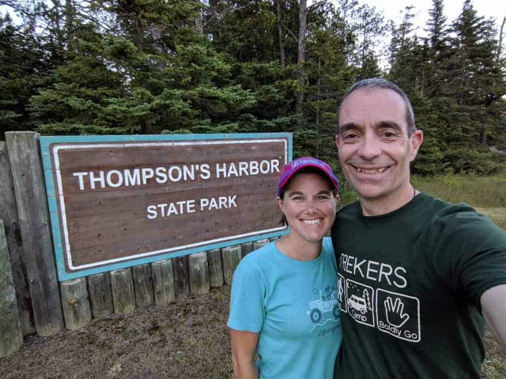 Two people in front of a sign that says Thompson's Harbor State Park