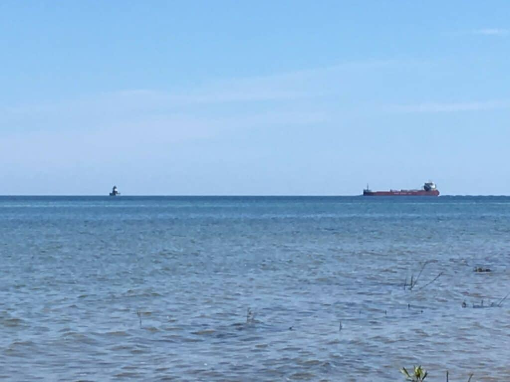 A picture of a freighter and a lighthouse in Lake Huron