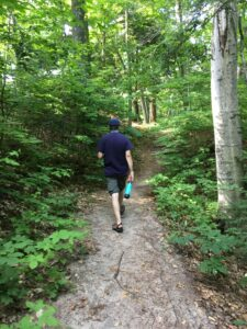 Man hiking on a trail in the woods