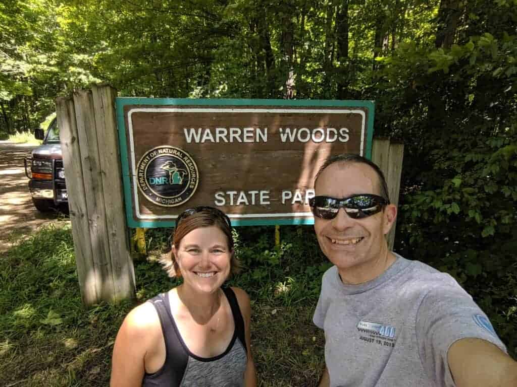 Two people by the state park entrance sign