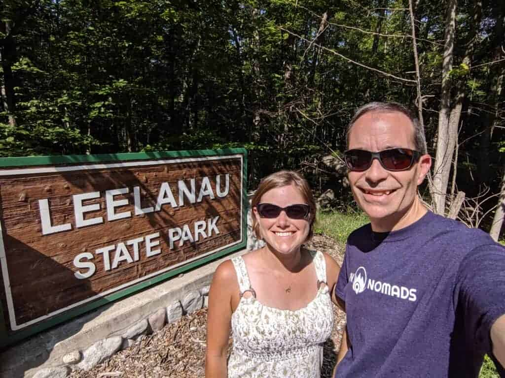 Two people by state park entrance sign
