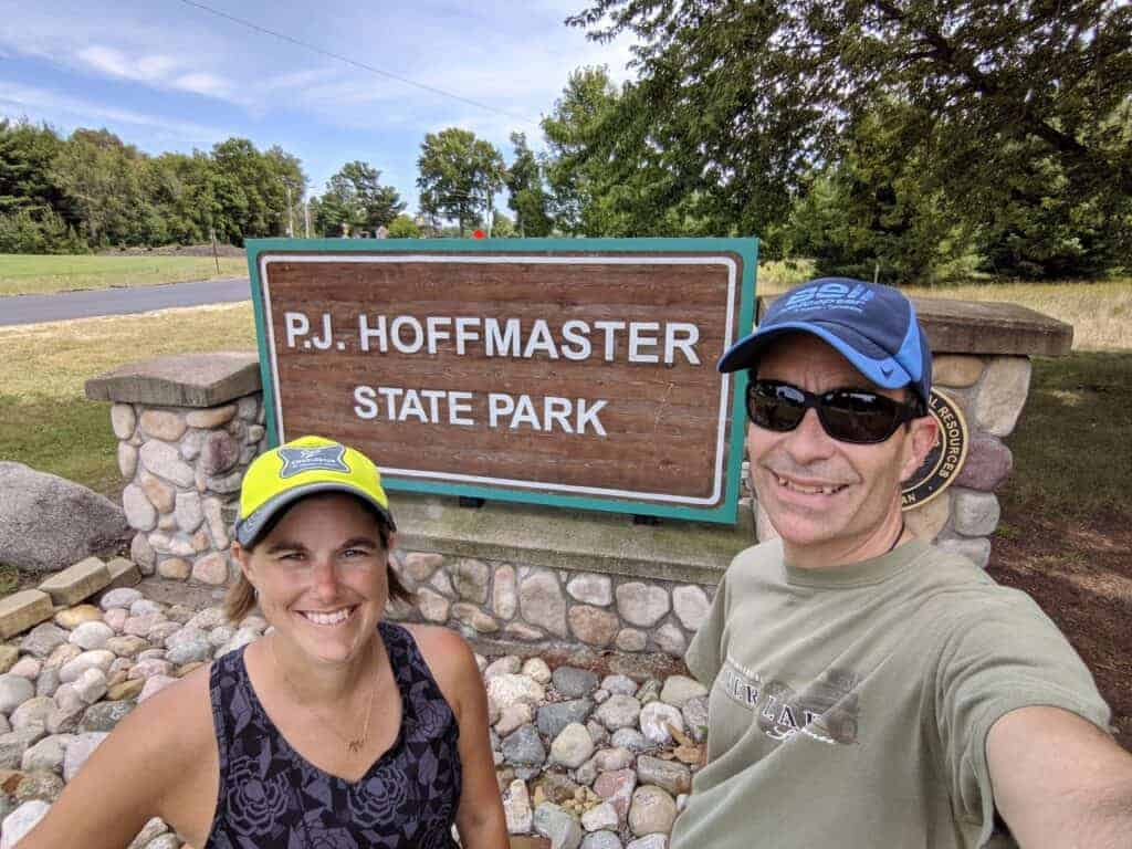 Two people in front of a state park sign