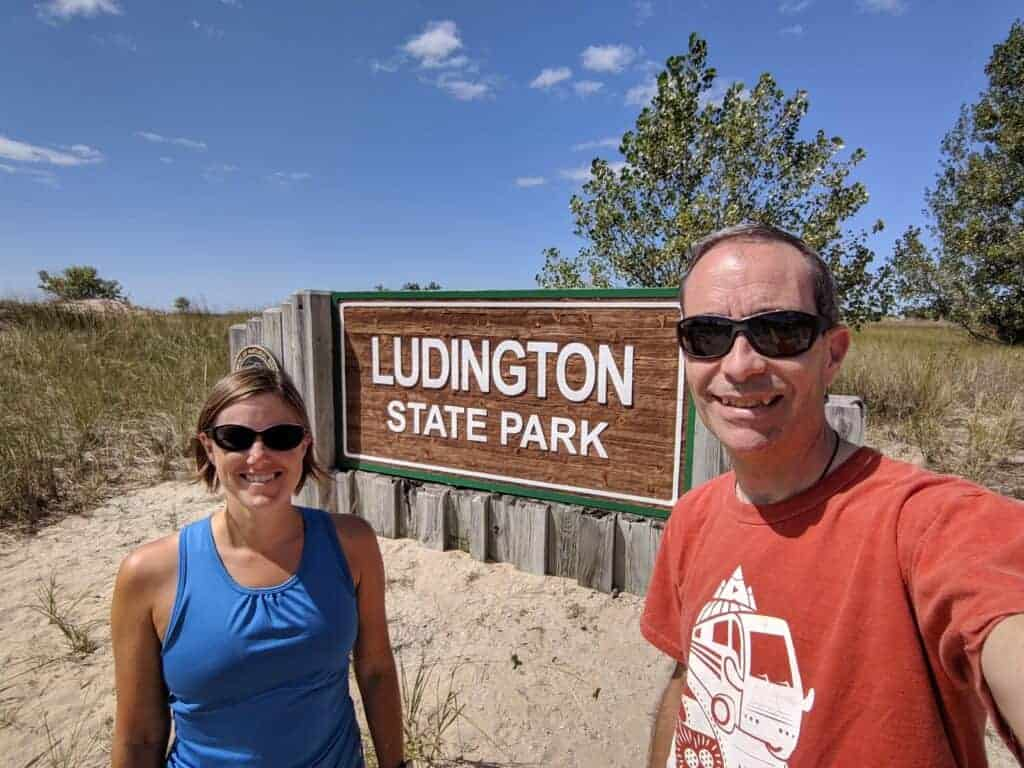 Two people by Ludington  State Park entrance sign