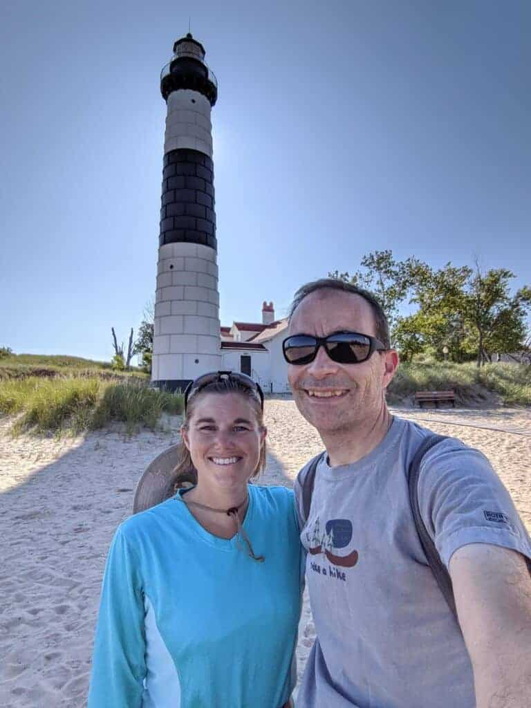 Two people by the Big Sable Point Lighthouse at Ludington State Park