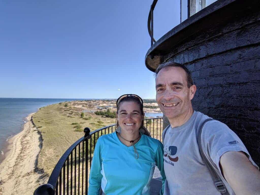 Two people by Big Sable Point Lighthouse at Ludington State Park