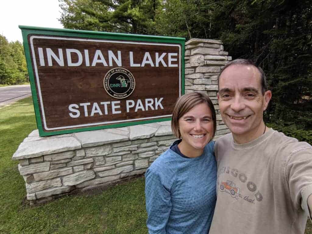 Two people by Indian Lake State Park Sign