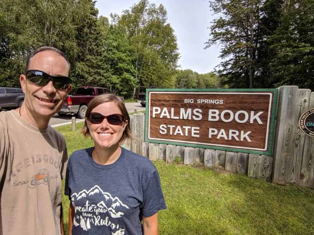 Two people by the Palms Book State Park sign