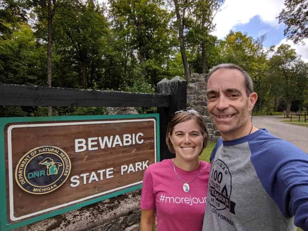 Two people by a state park entrance sign