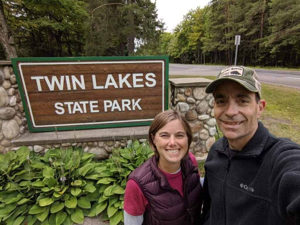 Two people by a state park sign