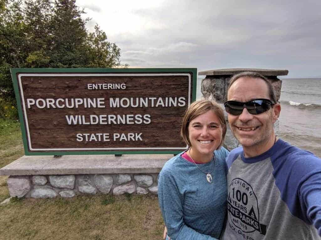A woman and man standing in front of the park entrance sign to Porcupine Mountains Wilderness State Park