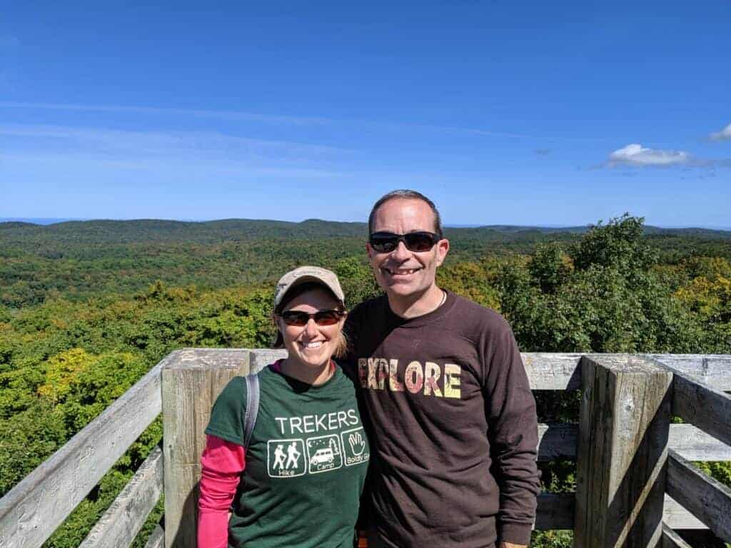 Man and woman smiling while standing in front of a large overlook of trees