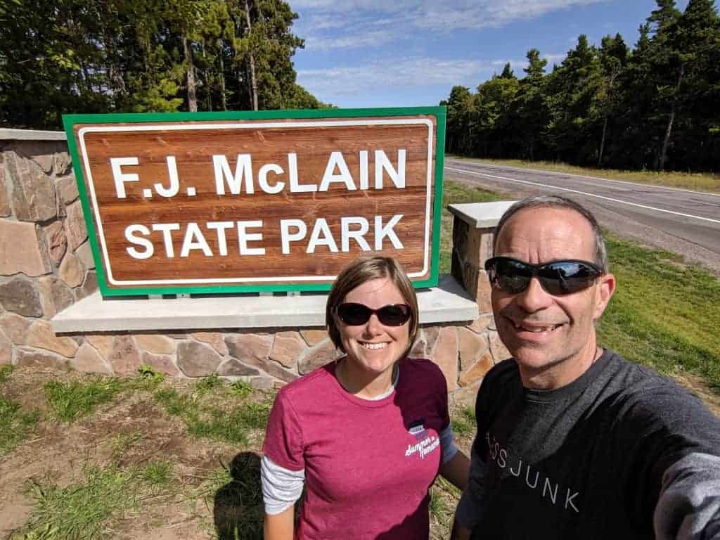A man and woman in front of the McLain State Park entrance sign