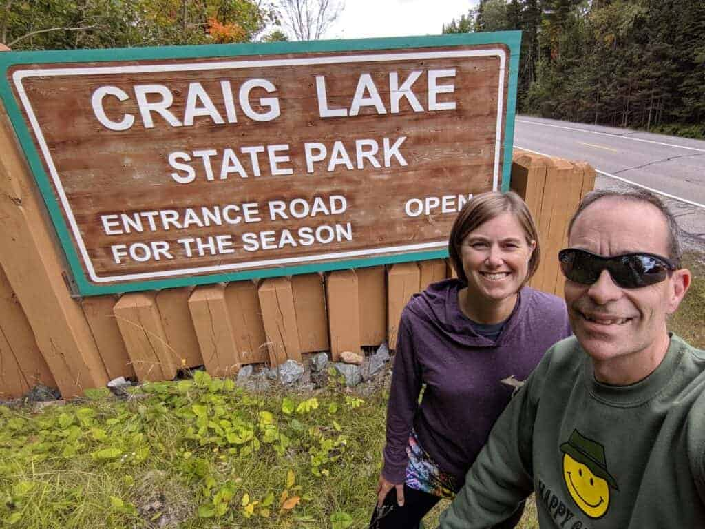 Two adults by the Craig Lake State Park entrance sign