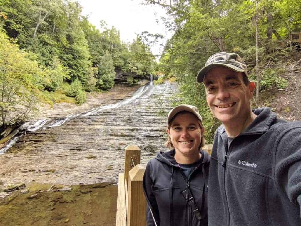 Two adults in front of Laughing Whitefish Falls