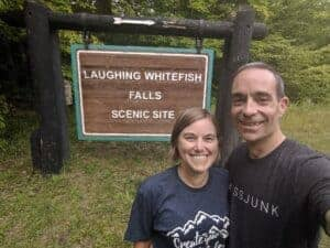 Two adults in front of Laughing Whitefish Falls entrance sign