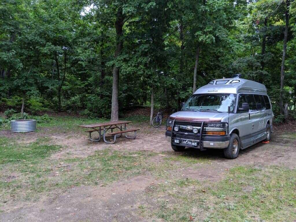 Roadtrek van in a campsite in the woods