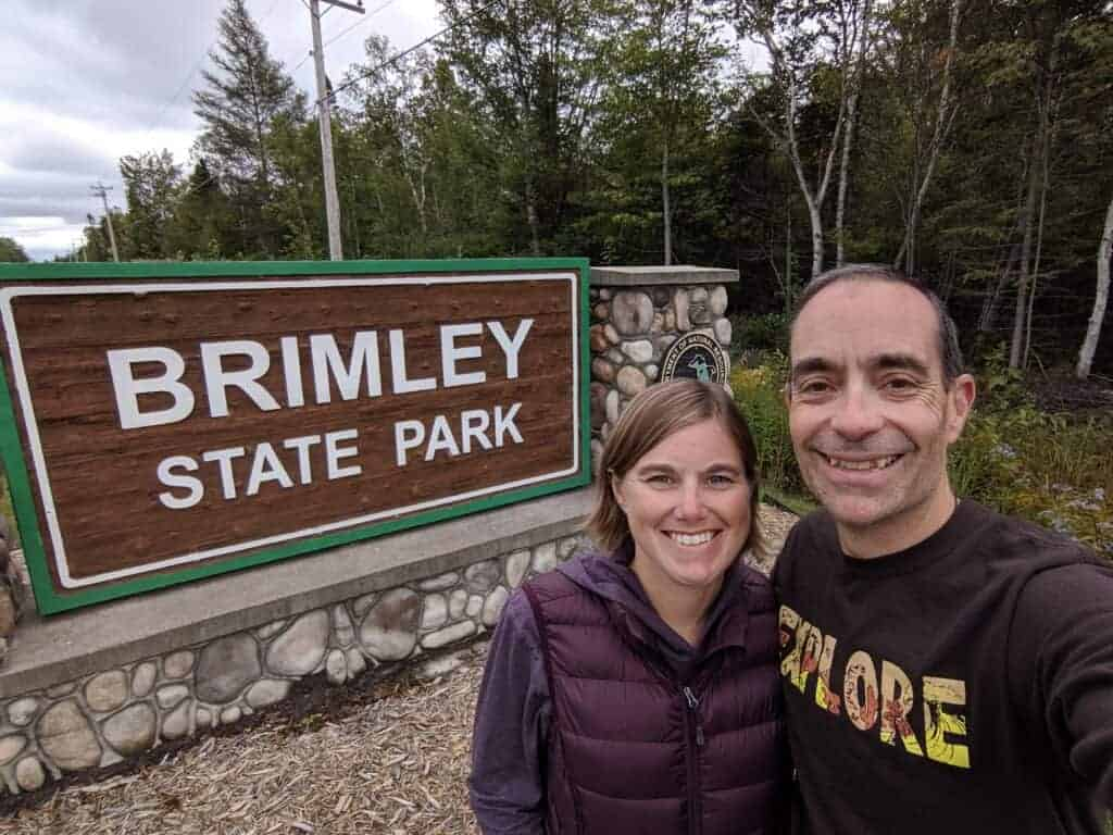 Two adults in front of the entrance sign at Brimley State Park