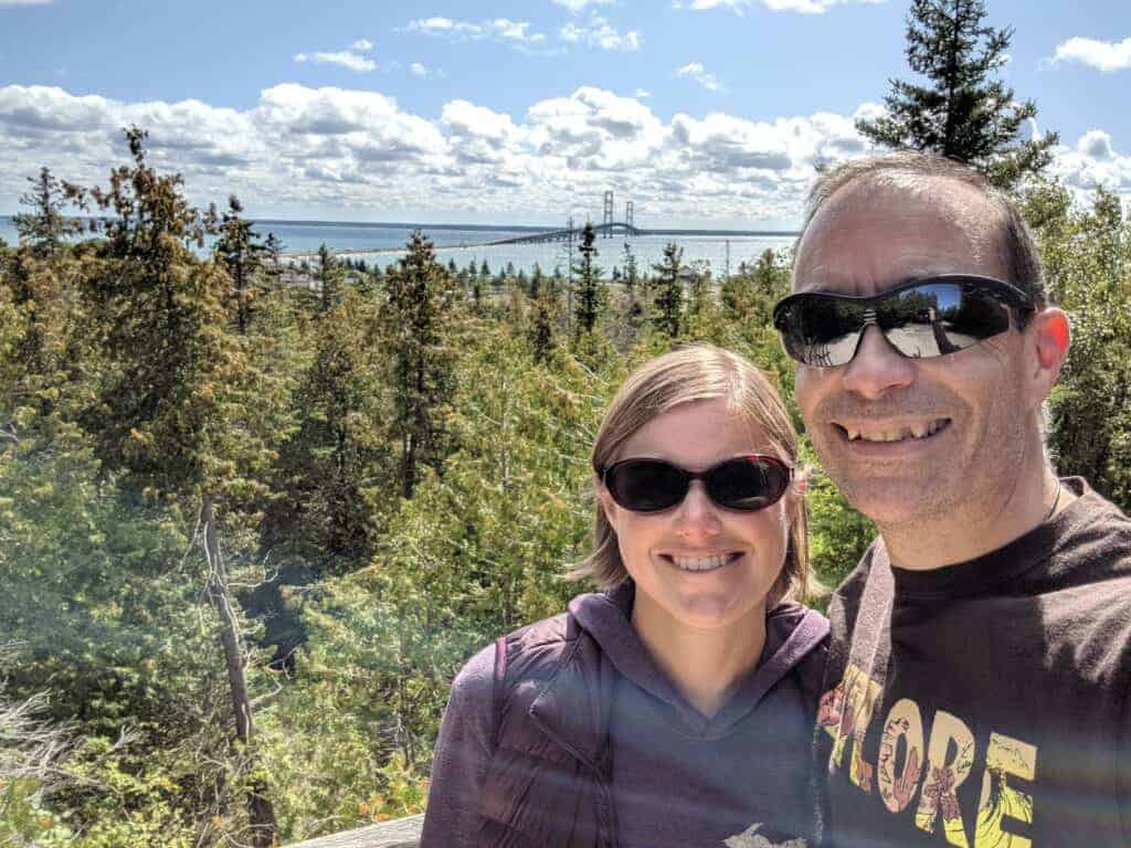 Two adults with the Mackinac Bridge behind them in the distance