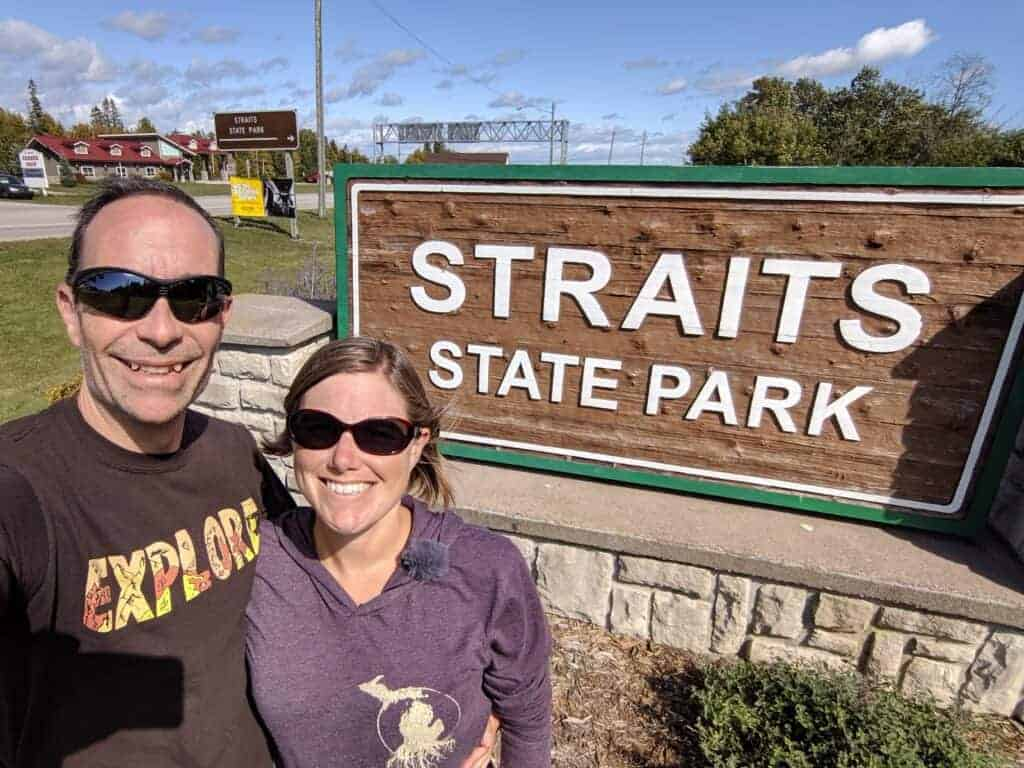 Two adults standing in front of the Straits State Park entrance sign