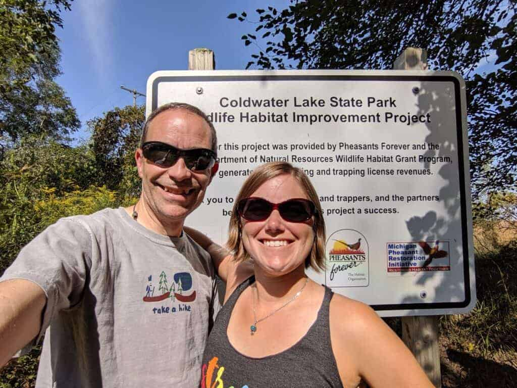 Two adults in front of Coldwater Lake State Park sign