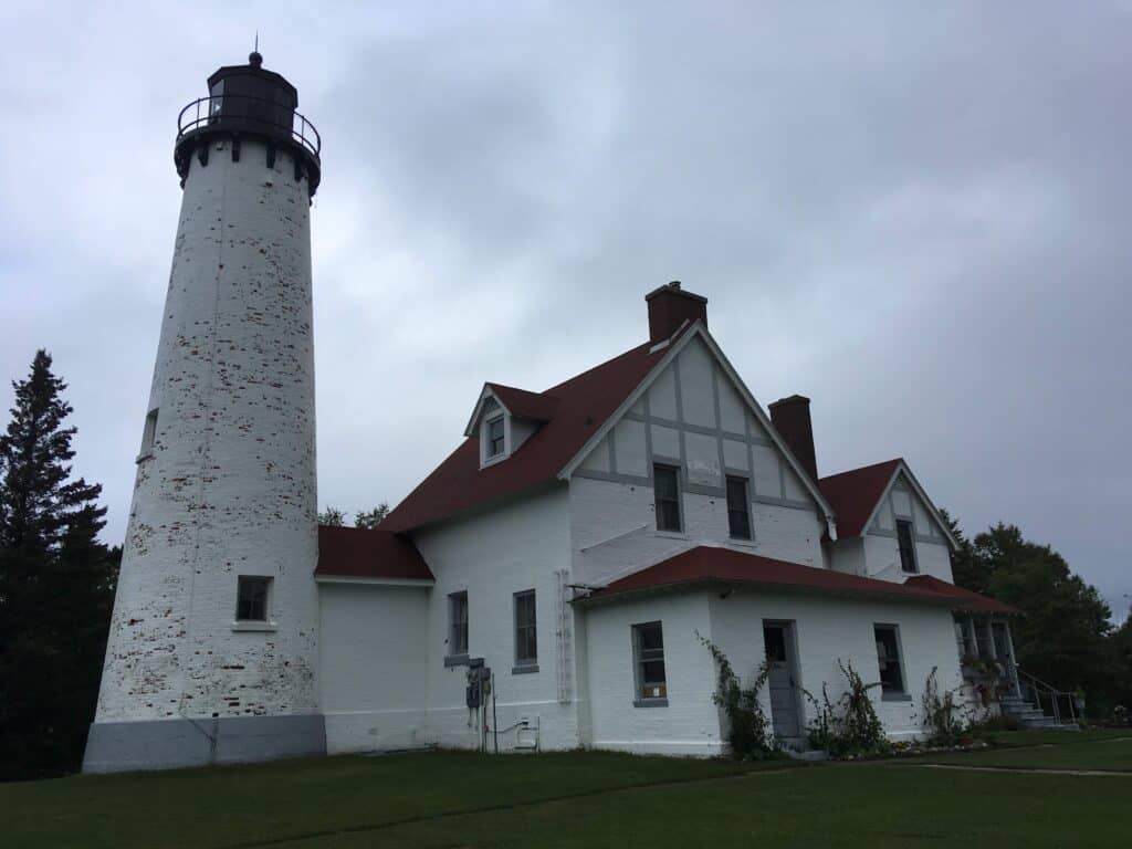 A white lighthouse and keepers building