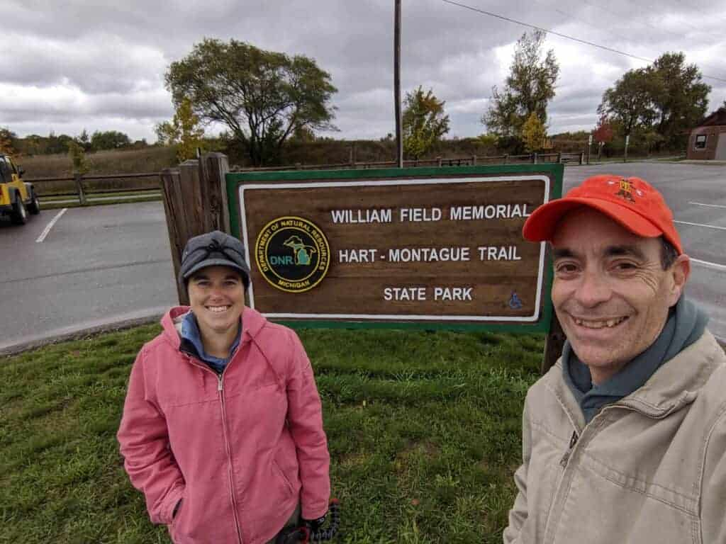 Man and Woman in front of a state park entrance sign