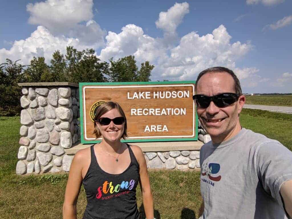 A man and woman in front of the Lake Hudson Recreation Area entrance sign
