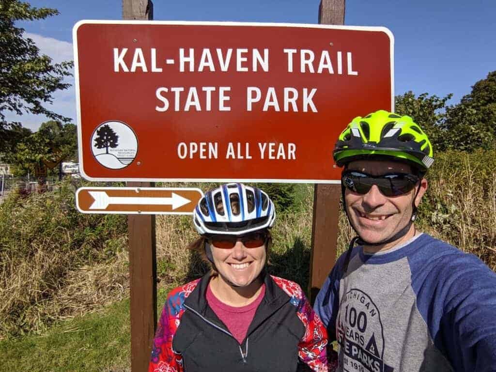 A man and woman in front of the Kal-Haven Trail state park entrance sign