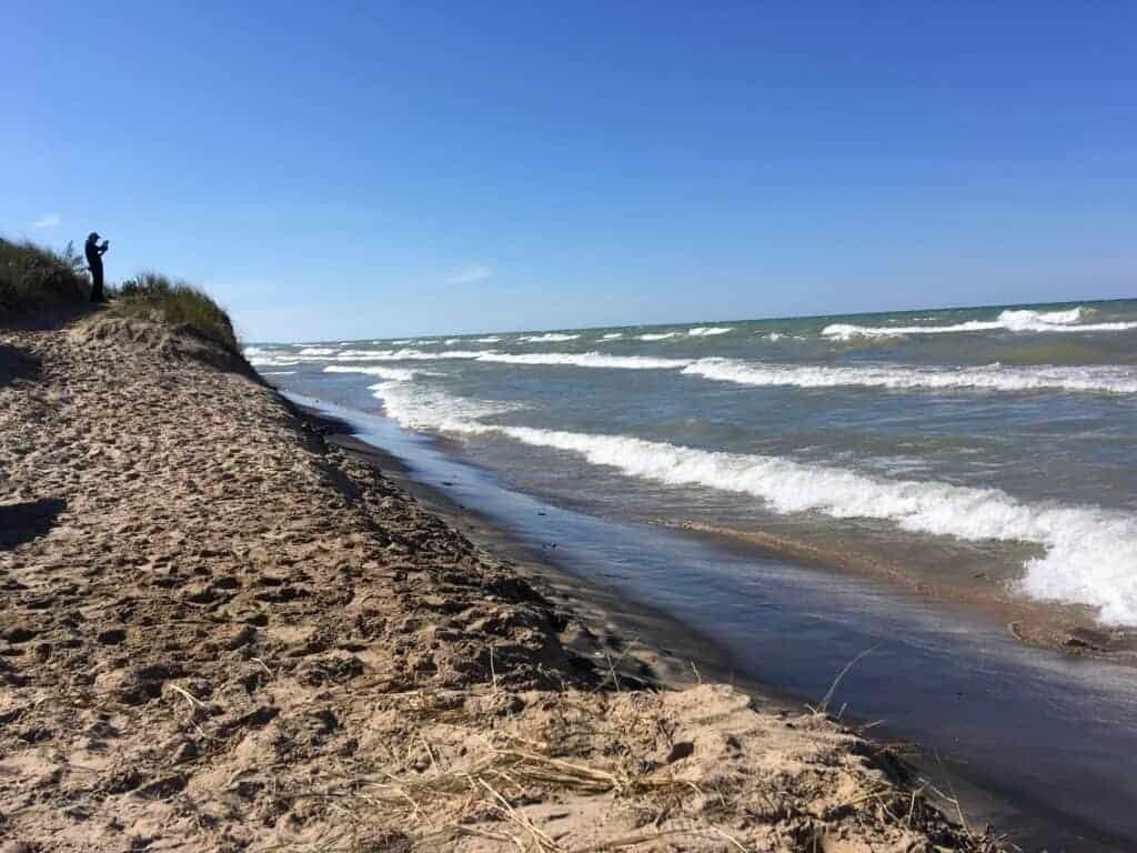 A sandy beach and waves on a lake