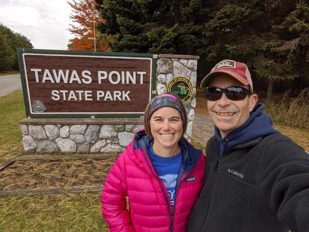 A male and female in front of Tawas Point State Park entrance sign