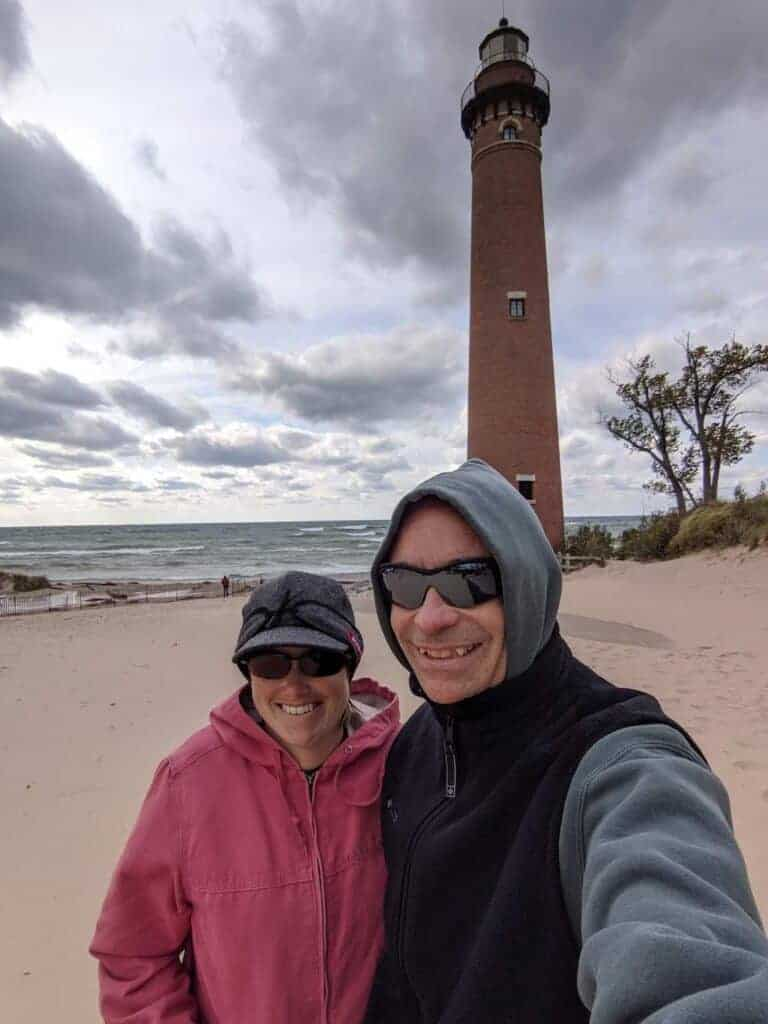 2 adults in front of Little Sable Point Lighthouse
