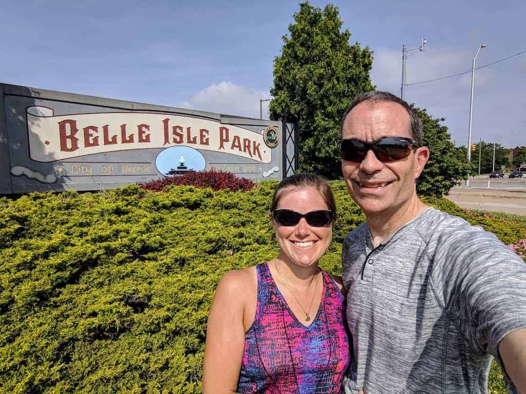 Two adults in front of Belle Isle Park entrance sign